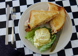 """The Aviator Café's signature sandwich, the """"Aviator,"""" is made with sliced turkey breast, tasty jalapeno bacon, provolone cheese, green chilies, chipotle mayonnaise and tomatoes. It's grilled and served hot on sourdough bread."""