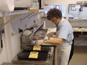 "Donna Pederson is grilling an ""Aviator Sandwich,"" the most popular item on the menu."