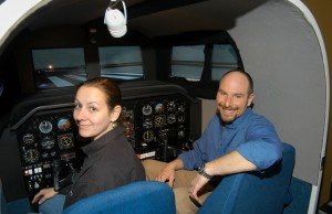 Sascha Protzko (right) and Megan Sayre, director of operations, practice flying in a virtual environment, using the flight school's AST HAWK flight training simulator.