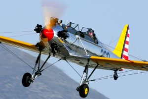The Commemorative Air Force Inland Empire Wing's 1941 Ryan PT-22 Recruit makes a low pass over the field.