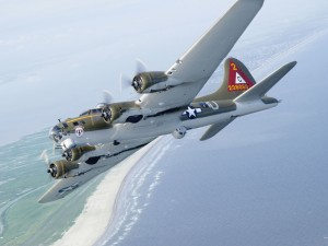 The Lone Star Flight Museum's B-17 cruises over the Gulf of Mexico shore.