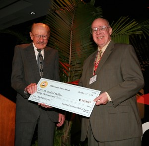 NAHF enshrinee Bob Hoover hands Dr. Richard Hallion his 2006 Combs Gates Award, a $20,000 check rewarding his aviation history research.