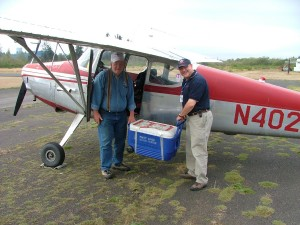 Command pilots Larry Holtz (left) and Christian Holtz (no relation) load blood from a Puget Sound Blood Center drive at Elma, Wash., into Larry's 1948 Cessna 170. After the pilots flew the blood to Boeing Field, it was driven to PSBC's lab in Renton.
