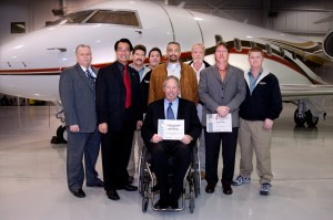Million Air Dallas President Jack Hopkins (seated) with, from left, Gene Lawson, airworthiness supervisor; Mayor Joe Chow; and Maintenance Technician Award recipients Steve Grandell, Ron MacAskill, Carlos Done, Bill Enckhausen, Bryan Boen and Blake Turner