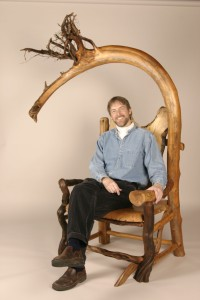 "Erik Lindbergh shows off his ""Dragon Throne,"" a chair made from cedar, locust, holly, juniper and pine."