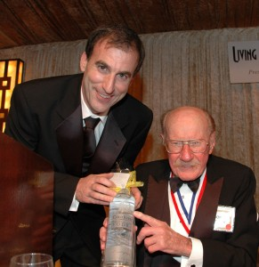 Don Thibodeau hands Bob Hoover a bottle of Cold River Vodka at the 2007 Living Legends of Aviation award ceremony. Inscribed specially for his 85th birthday, and bearing Hoover's likeness, the bottles were handed out to lucky guests.