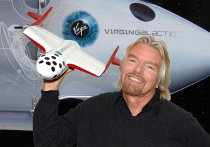 Richard Branson proudly holds a model of SS2, which will bear the Virgin Galactic name and is designed to travel strapped to the belly of WK2.