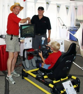 Dan Majka, an Experimental Aircraft Association director, and HotSeat inventor Jay LeBoff (right) shake hands while a young patron at KidVenture enjoys the flight simulator.