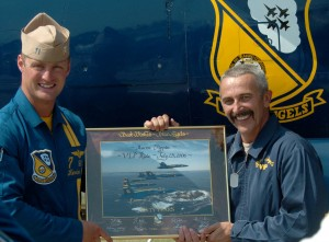Lt. Cmdr. Kevin Davis helps country singer and pilot Aaron Tippin display his VIP ride certificate at EAA AirVenture 2006.