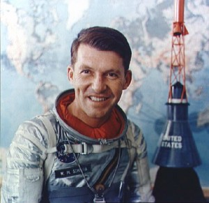In a formal portrait from the 1960s, Wally Schirra, in his Mercury pressure suit, poses in front of a Mercury spacecraft model.