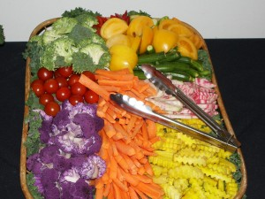 A colorful vegetable tray includes unusual items like purple cauliflower and yellow tomatoes, for an added bit of zest.