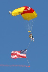 A member from the Just in Time Skydivers starts the show with an American flag.