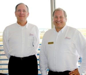 Dale Smith, Premier Aircraft Sales public relations manager (left), and Michael Fabianac, in front of their new regional sales office at Orlando Executive Airport.