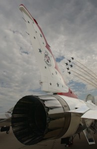 "A spare U.S. Air Force Thunderbird F-16 Fighting Falcon stands ready as the 2006 demonstration team performs its trademark ""Delta"" maneuver."