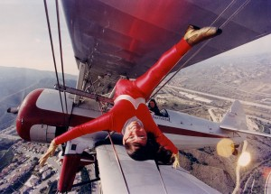 """In a maneuver performed only for air-to-air photography, Margi Stivers does """"the splits"""" in the middle of the Stearman's wings, while pilot and husband Hartley Folstad looks on."""