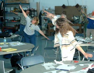 Teacher Sally Devore (front, left), a participant in the Science of Flight program at Paine field, joins other students in learning about aircraft angles, gravity and laws of motion in this exercise.