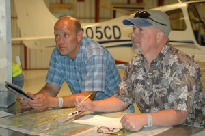 Navigation and aerial charts get a lot of attention from Dennis Sparks (left) and Daniel Guthrie as part of their summer familiarization classes on the world of aviation.