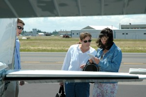 Teachers Michele Gates (left) and Phyllis Carr learn the details of checking out their plane before taking off from Paine Field.