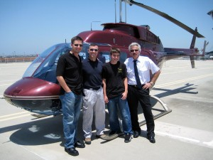 "Brian J. Terwilliger (left), producer and director of ""One Six Right,"" and Kevin LaRosa (right), aerial director and helicopter pilot, visit with Ian Hoey, sweepstakes grand prize winner, and his son Brennon."