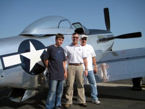 L to R: Ian Hoey, with son Brennon and Kevin LaRosa, can't help smiling after his ride in LaRosa's P-51 Mustang.