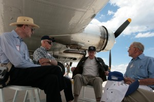 Members of the 8th Air Force Historical Society swap flying stories in the shade of the B-17's wing.