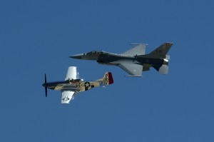 "Heritage Flight"" shows a P-51 Mustang and an F-16 Falcon sharing the sky at an air show in Grand Junction."