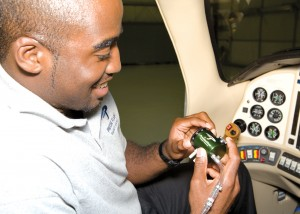 Barrington Irving holds up his Precise Flow Oxygen conserver made by Precise Flight. Hundreds of manufacturers including Precise Flight, Goodyear, Avidyne and Teledyne Continental Motors donated components to Irving's plane.