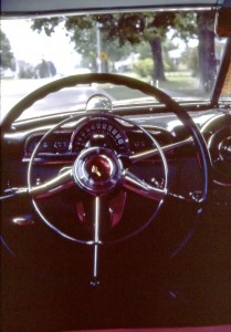 The prism atop the Pontiac Eight's steering column views stoplights blocked by the car's external sun visor.