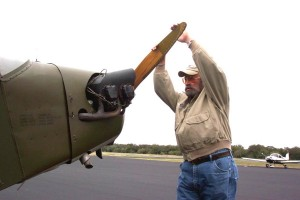Don Johnson hand props the engine before Jim Stegall's ride in the L-4 Cub. Jay Carpenter's Tiger is in the background.