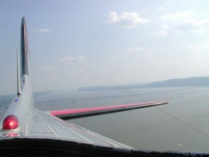 This view is from the Yankee Lady, heading north after passing over the Tappan Zee Bridge, in the background. Although Yankee Lady never flew in the war, the nose art and aircraft markings are typical of the kind painted during WWII.