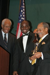 Col. Guion S. Bluford (left) looks on as the designer and namesake of the Ed Dwight Jr. Award presents it to Barrington Irving (center).