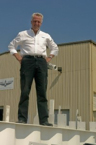 """Jerry Curtis is on top of the world and on top of one of his """"wavy-web"""" trusses. The innovative design allows for tremendously increased open spans in large buildings."""