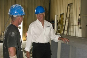 Superior quality is a top requirement for EagleSpan. Jerry Curtis (right) discusses a finished beam with Mark Dodson, production paint line manager.