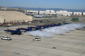 The Blue Angels show begins on the ground, demonstrating precision while marching to the planes, getting in the cockpits starting the engines, and maintaining a synchronized puff of smoke during takeoff, even though the air show crowds are miles away.