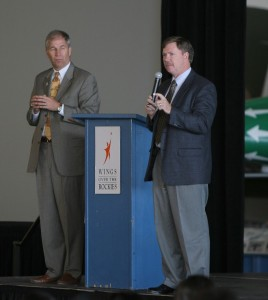 Greg Anderson (left), president and CEO of Wings Over the Rockies, looks on as Aurora Public Schools Superintendent John Barry addresses his students.