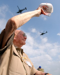 "Brig. Gen. Tex Hill waves a ""Flying Tigers"" hat at Apaches overhead from the 8-229th Aviation Regiment. The occasion was his 91st birthday party, held in Dayton, Ohio, in July 2006, the same week he was enshrined into the National Aviation Hall of fame."