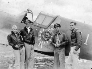 "L to R: John Alison, Maj. Tex Hill, Ajax Baumler and Mack Mitchell, at Kunming in July 1942, pose in front of a P-40 bearing the original 23rd Fighter Group logo, a Disney tiger wearing an ""Uncle Sam"" hat, tearing through a Chinese Sun."
