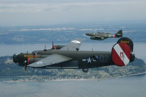 Cruising in formation over Whidbey Island, with Paine Field in the background, this B-24 Liberator and Me 262 Stormbird present an unusual view of these World War II adversaries.