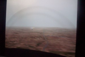 The large projected display seen through the FTD windshield shows major local terrain, and in this case, ground haze selected by the instructor.