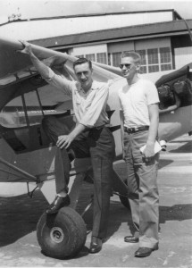 Stan Sears (on the left) and another student take time out from lessons to get their picture taken in front of a Piper J-3 Cub.