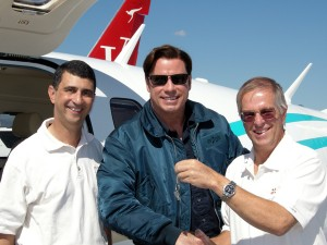 Vern Raburn (right), founder and CEO of Eclipse Aviation, accompanied by Mike McConnell (left), VP of marketing and sales hands, hands John Travolta the keys to his new Eclipse 500.