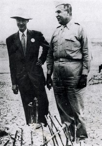 Nuclear physicist J. Robert Oppenheimer (left) converses with Col. Leslie Groves beside the remains of the tower used to set off the world's first atomic explosion on the Alamogordo bombing range.