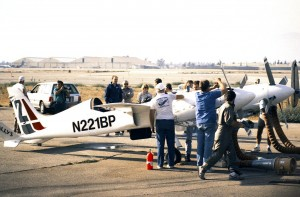 1986 National Champion Rick Brickert (standing with Bruce Boland behind cockpit) and the Planes of Fame crew review the Pond Racer following flight-testing east of Chino, Calif., prior to the 1991 Reno Air Races.