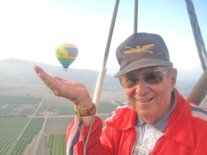 In a hot air balloon above Santa Paula, Calif, Fred Blechman strikes a humorous pose, making it look like the distant companion balloon is about to land on his hand.