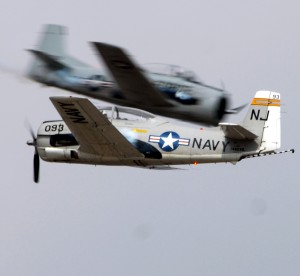 "In a daring ""heart cross"" maneuver performed at the 2007 EAA AirVenture Oshkosh, Trojan Horseman Jack ""Skids"" Mitchard, in the Navy plane in the foreground, appears breathlessly close to Dr. Ralph ""Skydoc"" Glasser in the blurred Air Force T-28."
