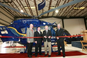 L to R: Stu Eickelberg, procurement administrator for Mayo Clinic; Paul Drucker, program director for Mayo Clinic medical transport; and Arthur Torwirt, vice president of Air Methods Products Division, look on as Dr. Dan Hankins cuts the ribbon.