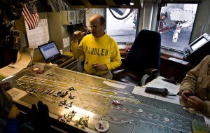 "Lt. Derek Jensen, the aircraft handling officer, utilizes a scale model of the flight deck, commonly called the ""Ouija board,"" to coordinate placement and movement of aircraft."
