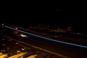 An F/A-18 aircraft touches down during a time exposure of night flight operations. The aircraft-arresting hook striking the steel flight deck causes the sparks.