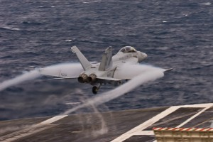 An F/A-18E Super Hornet of Strike Fighter Squadron 22 (VFA-22), the Fighting Redcocks, exhibits some condensation during a launch from the waist catapult.