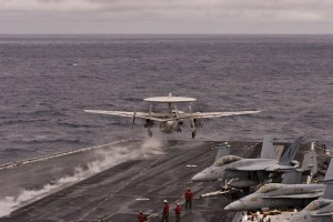 An E-2C Hawkeye aircraft of Carrier Airborne Command and Control Squadron 113 (VAW-113), the Black Eagles, launches from the number 2 catapult at the beginning of flight operations.